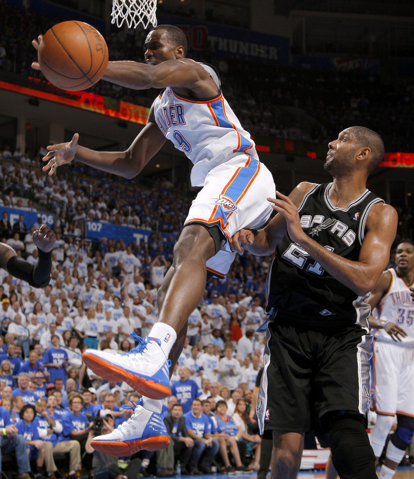 Photo - Oklahoma City's Serge Ibaka (9) leaps for the ball in front of San Antonio's Tim Duncan (21) during Game 4 of the Western Conference Finals between the Oklahoma City Thunder and the San Antonio Spurs in the NBA playoffs at the Chesapeake Energy Arena in Oklahoma City, Saturday, June 2, 2012. Oklahoma CIty won 109-103. Photo by Bryan Terry, The Oklahoman