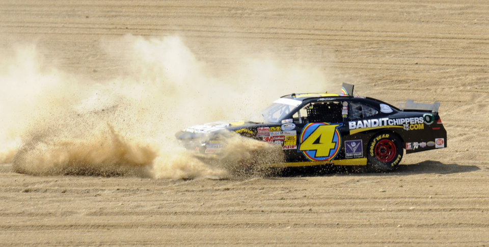 Photo - Jeffrey Earnhardt slides through the gravel pit after going off course in turn four during the NASCAR Nationwide Series Nationwide Children's Hospital 200 auto race at Mid-Ohio Sports Car Course Saturday, Aug. 16, 2014 in Lexington, Ohio. (AP Photo/Tom E. Puskar)