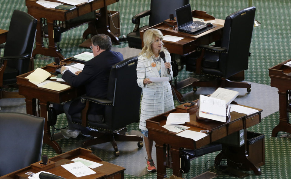 Photo - Sen. Wendy Davis, D-Fort Worth, stands on a near empty senate floor as she filibusters in an effort to kill an abortion bill, Tuesday, June 25, 2013, in Austin, Texas. The bill would ban abortion after 20 weeks of pregnancy and force many clinics that perform the procedure to upgrade their facilities and be classified as ambulatory surgical centers.  (AP Photo/Eric Gay)