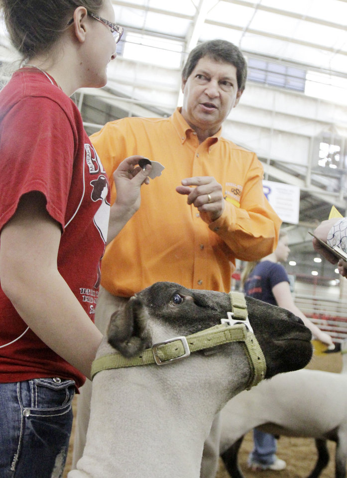 Photo - Jerry Fitch, one of four sheep superintendents at Oklahoma Youth Expo, talks breeds with a student prior to the first round of judging March 15.  PAUL HELLSTERN - Oklahoman