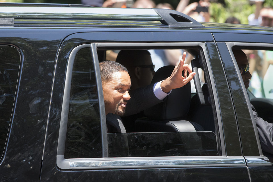 Photo - Actor Will Smith greets the crowd as he takes part in Muhammad Ali's funeral procession while they enter Cave Hill Cemetery, Friday, June 10, 2016, in Louisville, Ky. (AP Photo/John Minchillo)