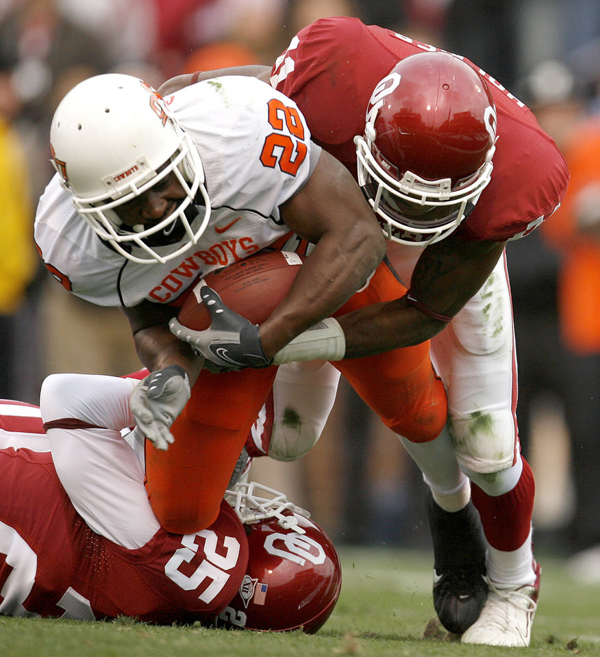 Photo - Dantrell Savage of OSU is brought down by D.J. Wolfe, left, and Lendy Holmes of OU during the first half of the college football game between the University of Oklahoma Sooners (OU) and the Oklahoma State University Cowboys (OSU) at the Gaylord Family-Memorial Stadium on Saturday, Nov. 24, 2007, in Norman, Okla.  Photo By Bryan Terry, The Oklahoman