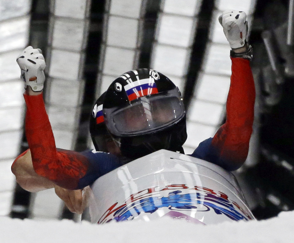 The team from Russia RUS-1, piloted by Alexander Zubkov and brakeman Alexey Voevoda, cross into the finish area to win the gold medal during the men's two-man bobsled competition at the 2014 Winter Olympics, Monday, Feb. 17, 2014, in Krasnaya Polyana, Russia. (AP Photo/Dita Alangkara)
