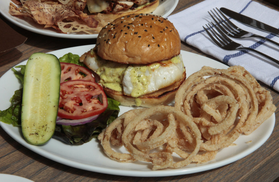 Photo - The fresh grouper sandwich is served on a house-made sesame bun with caper aioli and a side of onion rings.  David McDaniel - The Oklahoman