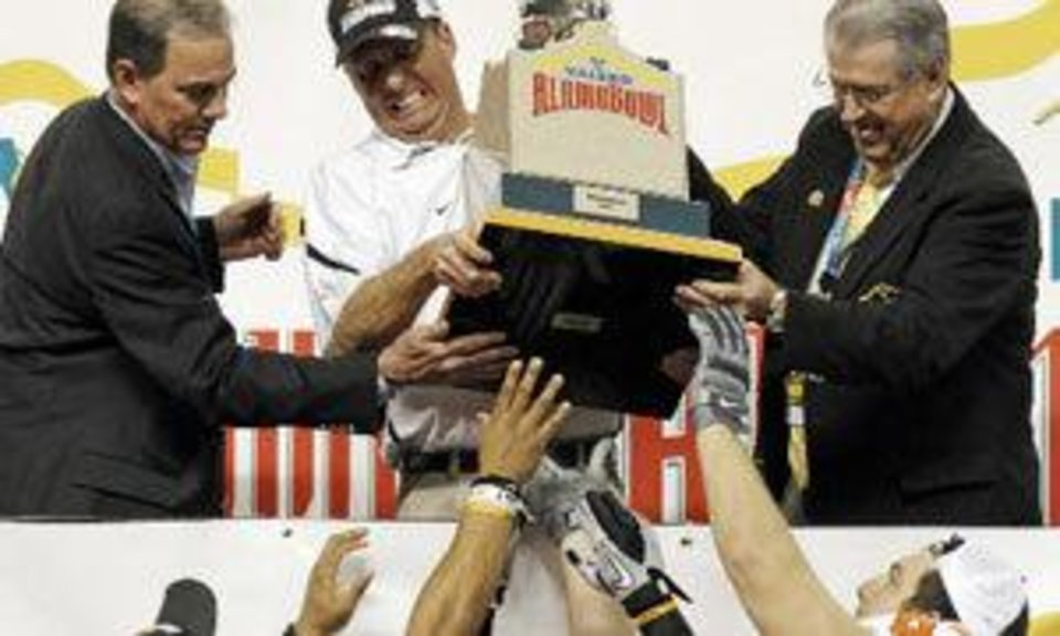 OSU head coach Mike Gundy hands the trophy to Mathies Long (35), Bo Bowling (9) and Jordan Taormina (63) after the Valero Alamo Bowl college football game between the Oklahoma State University Cowboys ( OSU) and the University of Arizona Wildcats at the Alamodome in San Antonio, Texas, Wednesday, December 29, 2010. OSU won, 36-10. Photo by Nate Billings