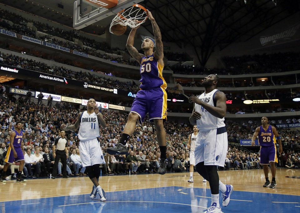 Photo - Los Angeles Lakers' Robert Sacre (50) goes up for an uncontested dunk as Dallas Mavericks' Monta Ellis (11) and DeJuan Blair, right, watch in the first half of an NBA basketball game, Tuesday, Jan. 7, 2014, in Dallas. (AP Photo/Tony Gutierrez)