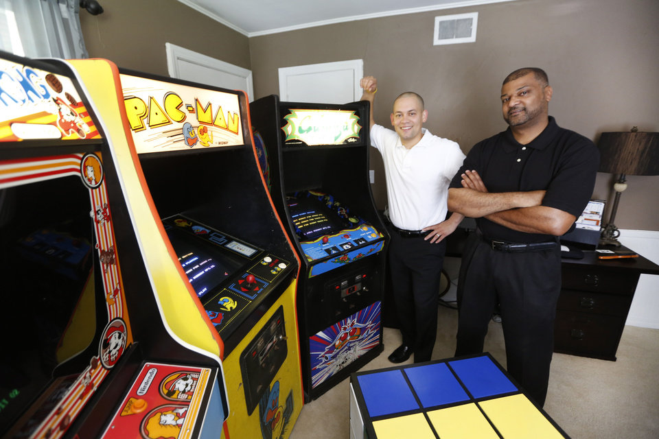 Photo - Jose Rodriguez, left, and Mark Temple pose with 1980s video games Wednesday. They plan to open an '80s themed bar on NW 23. Photo By Steve Gooch, The Oklahoman  Steve Gooch