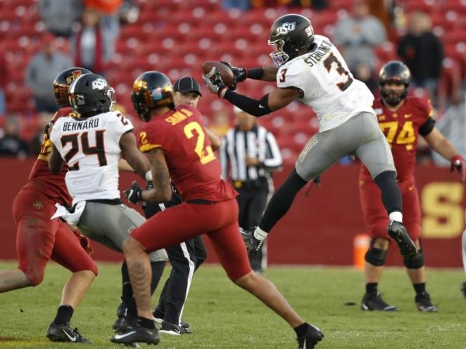 Photo -  Oklahoma State safety Tre Sterling, right, leaps for an interception in the second half of a 34-27 win Saturday at Iowa State. [AP Photo/Matthew Putney]