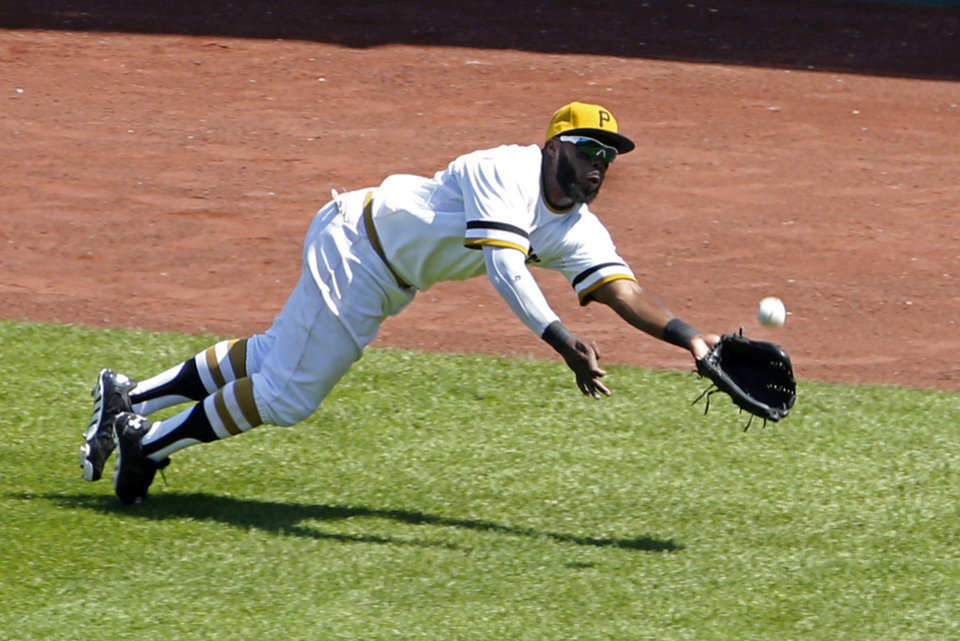 Photo - Pittsburgh Pirates right fielder Josh Harrison dives for a fly ball hit by Washington Nationals' Ian Desmond during the sixth inning of a baseball game in Pittsburgh Sunday, May 25, 2014. Harrison made the catch but lost the ball when his glove hit the ground. Desmond was credited with a run batted in and a single. The Nationals won 5-2. (AP Photo/Gene J. Puskar)