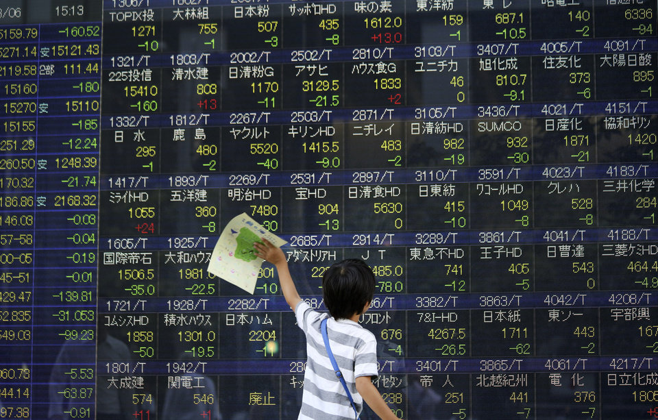 Photo - A child plays in front of an electronic stock board of a securities firm in Tokyo, Wednesday, Aug. 6, 2014. Worries over Russian troops amassing near the Ukraine border sent most Asian stock markets lower Wednesday. (AP Photo/Eugene Hoshiko)