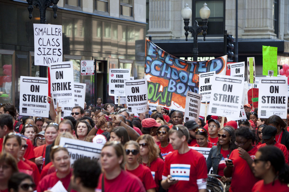 Photo -   Thousands of public school teachers march on streets surrounding the Chicago Public Schools district headquarters on the first day of strike action over teachers' contracts on Monday, Sept. 10, 2012 in Chicago. For the first time in a quarter century, Chicago teachers walked out of the classroom Monday, taking a bitter contract dispute over evaluations and job security to the streets of the nation's third-largest city — and to a national audience — less than a week after most schools opened for fall. (AP Photo/Sitthixay Ditthavong)