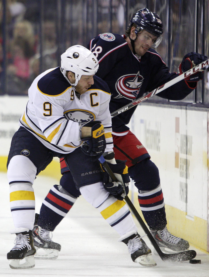 Photo - Buffalo Sabres' Steve Ott, left, and Columbus Blue Jackets' Boone Jenner fight for a loose puck during the first period of an NHL hockey game, Saturday, Jan. 25, 2014, in Columbus, Ohio. (AP Photo/Jay LaPrete)