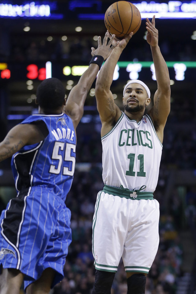 Photo - Boston Celtics guard Jerryd Bayless (11) takes a shot at the basket as Orlando Magic guard E'Twaun Moore (55) tries to block him in the first quarter of an NBA basketball game, Sunday, Feb. 2, 2014, in Boston. (AP Photo/Steven Senne)