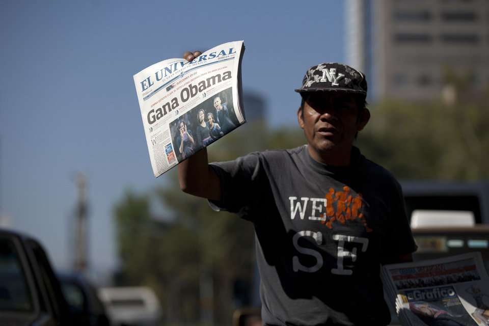"A newspaper vendor sells dailies with the front page showing President Barack Obama that reads in Spanish ""Obama Wins"" one day after U.S. elections in Mexico City, Wednesday Nov. 7, 2012. (AP Photo/Eduardo Verdugo)"