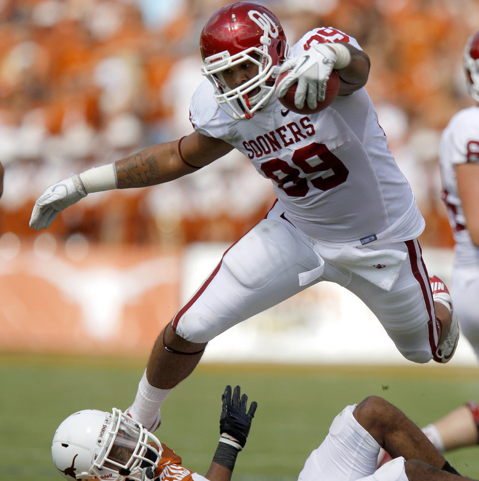 Photo - Oklahoma's Austin Haywood (89) leaps over Texas' Carrington Byndom (23) during the Red River Rivalry college football game between the University of Oklahoma Sooners (OU) and the University of Texas Longhorns (UT) at the Cotton Bowl in Dallas, Saturday, Oct. 8, 2011. Oklahoma won 55-17. Photo by Bryan Terry, The Oklahoman