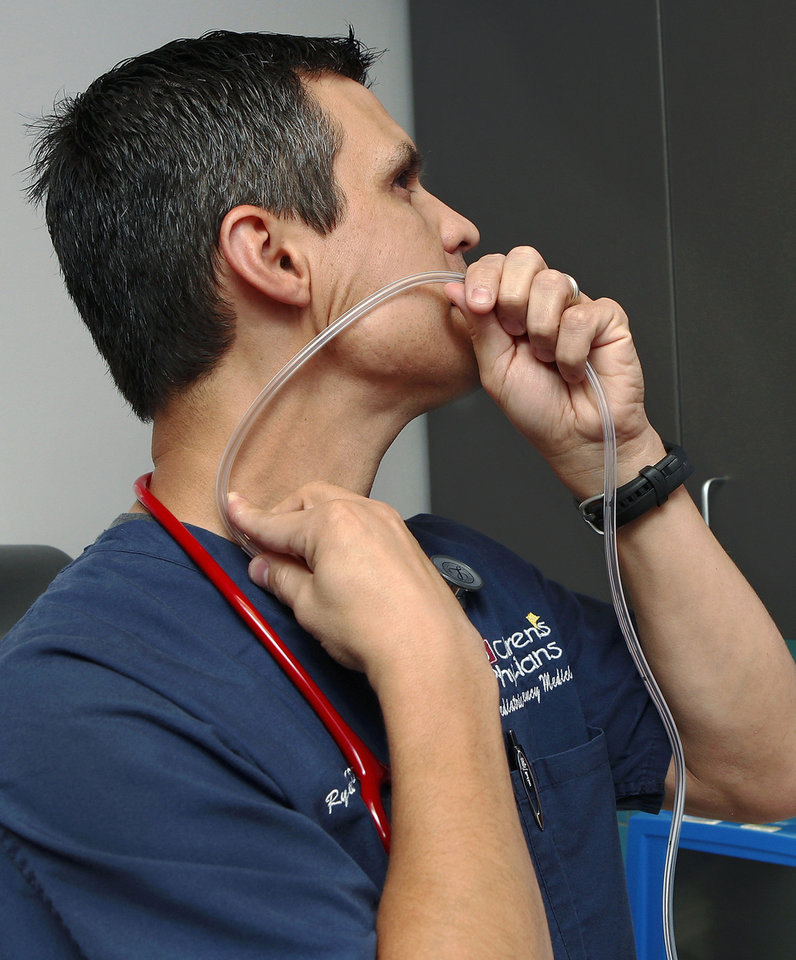 Photo - Dr. Ryan Brown, emergency room physician at Children's Hospital demonstrates  the technique for performing a gastric lavage, commonly referred to as