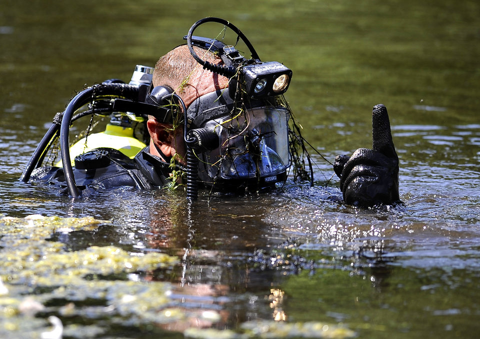 Photo - Connecticut State Police Dive Team continue to search for the second day, Pine Lake in Bristol, Conn., the hometown of the former New England Patriots player Aaron Hernandez,  Tuesday, July 30, 2013. Authorities have declined to comment on the search except to confirm it is related to the Hernandez investigation.  Hernandez has pleaded not guilty to murder in the death of Odin Lloyd, a 27-year-old Boston semi-professional football player. (AP Photo/Jessica Hill)