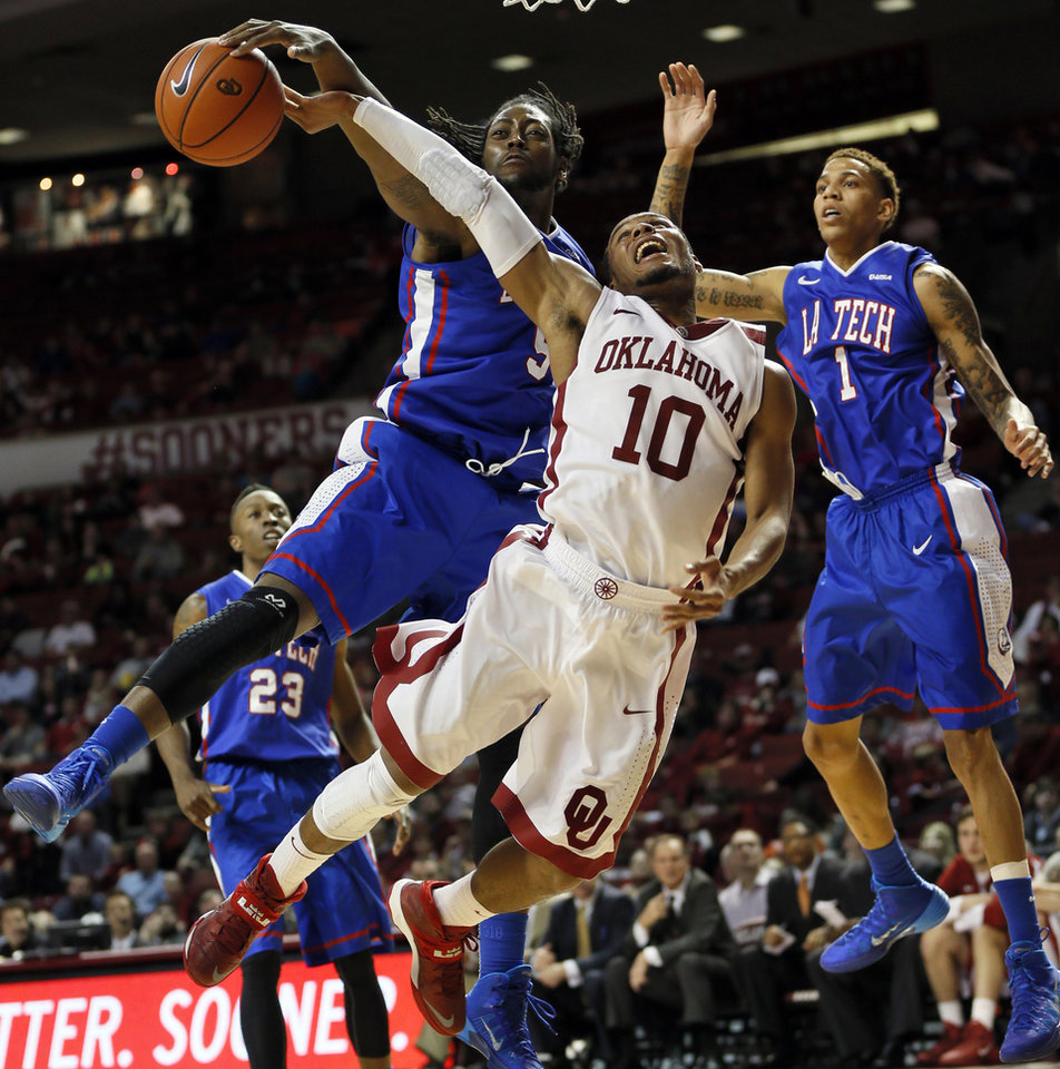 Louisiana Tech�s Chris Anderson, left, fouls OU�s Jordan Woodard, center, during Monday night�s game. Louisiana Tech won 102-98 in overtime.  Photo by Nate Billings, The Oklahoman