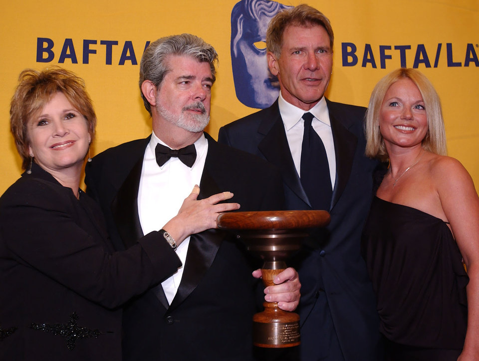 Photo - After receiving the Stanley Kubrick Britannia Award for Excellence in Film, George Lucas, second from left, poses with actress Carrie Fisher, left, actor Harrison Ford and singer Geri Halliwell, backstage at the BAFTA/LA 11th Annual Britannia Awards, Friday, April 12, 2002, in Beverly Hills, Calif. (AP Photo/Lucy Nicholson)