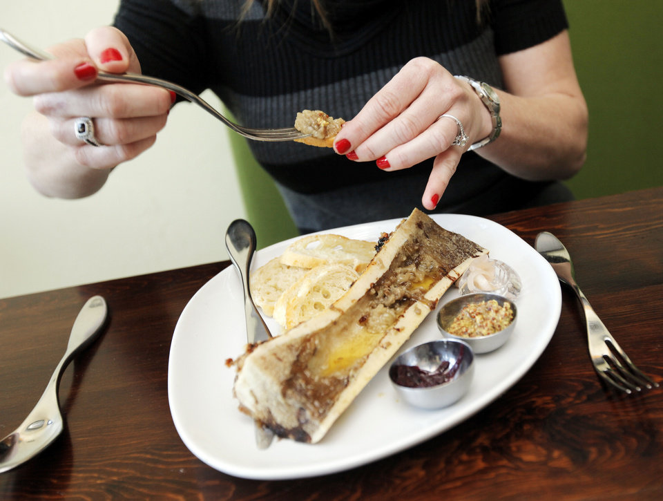Photo - Erica Millar eats Roasted Bone Marrow for the first time at Ludivine.  NATE BILLINGS - THE OKLAHOMAN