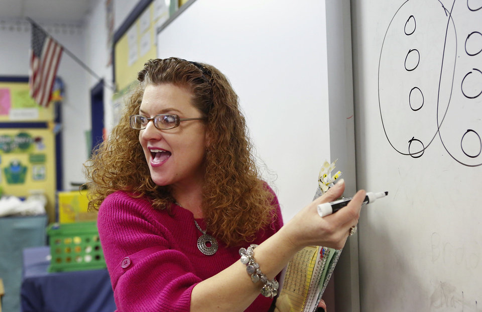 Photo - Sallie Harrison, a fourth-grade science and math teacher at Meeker Elementary School, explains long division to her students. Harrison has has multiple sclerosis.    Photo by Jim Beckel, The Oklahoman  Jim Beckel - THE OKLAHOMAN
