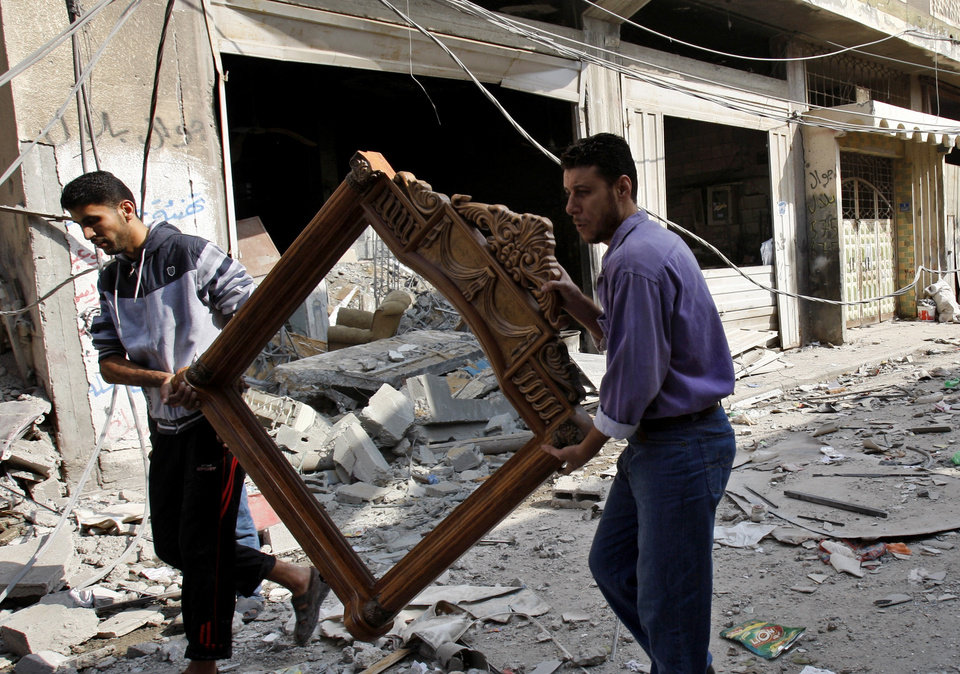 Photo -   Palestinians carry a frame from the destroyed house of Islamic Jihad militant Hasam Al Kholy, hit overnight in an Israeli strike on Gaza City, Tuesday, Nov. 20, 2012. Efforts to end a week-old convulsion of Israeli-Palestinian violence drew in the world's top diplomats on Tuesday, with President Barack Obama dispatching his secretary of state to the region on an emergency mission and the U.N. chief appealing from Cairo for an immediate cease-fire.(AP Photo/Adel Hana)