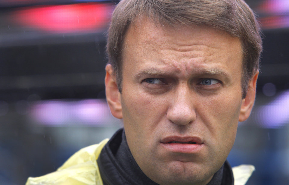 Photo - Russian opposition leader Alexei Navalny, in a raincoat, waits for the start of his last rally in rain-soaked Moscow, Russia, Friday, Sept. 6, 2013. The anti-corruption blogger and a leader of the Russian protest movement, Navalny will face the incumbent Mayor Sergei Sobyanin, in the upcoming Moscow's mayoral election on Sept. 8. (AP Photo/Sergei Grits)