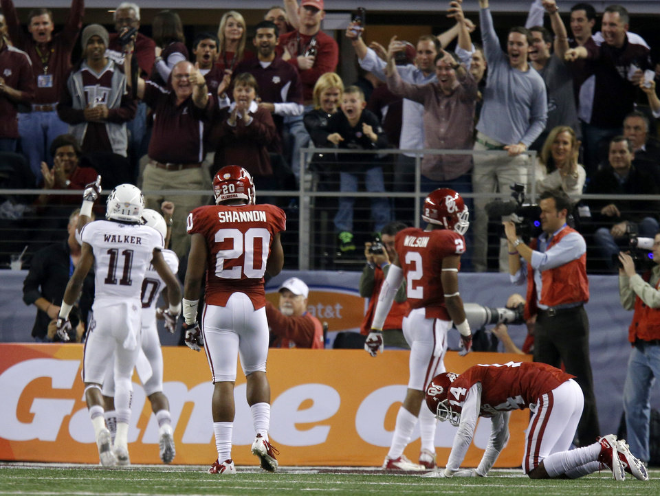 Photo - Oklahoma's Aaron Colvin (14) hangs his head as Texas A&M fans celebrate a touchdown by Texas A&M 's Trey Williams (20) during the Cotton Bowl college football game between the University of Oklahoma (OU)and Texas A&M University at Cowboys Stadium in Arlington, Texas, Friday, Jan. 4, 2013. Oklahoma lost 41-13. Photo by Bryan Terry, The Oklahoman