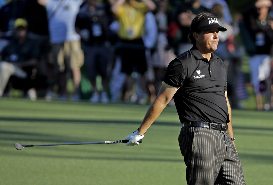 Photo - Phil Mickelson reacts after putting his third shot into the water on the 15th hole during the first round of the Masters golf tournament Thursday, April 10, 2014, in Augusta, Ga. (AP Photo/David J. Phillip)