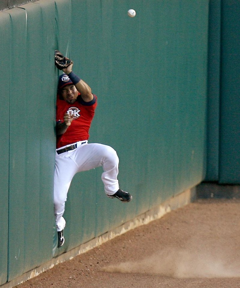 Hernan Iribarren of the Oklahoma City RedHawks hits the wall as he misses a foul ball in the third inning of a minor league baseball game against the Iowa Cubs at the AT&T Bricktown Ballpark in Oklahoma City on Saturday, July 31, 2010.  Photo by Bryan Terry, The Oklahoman
