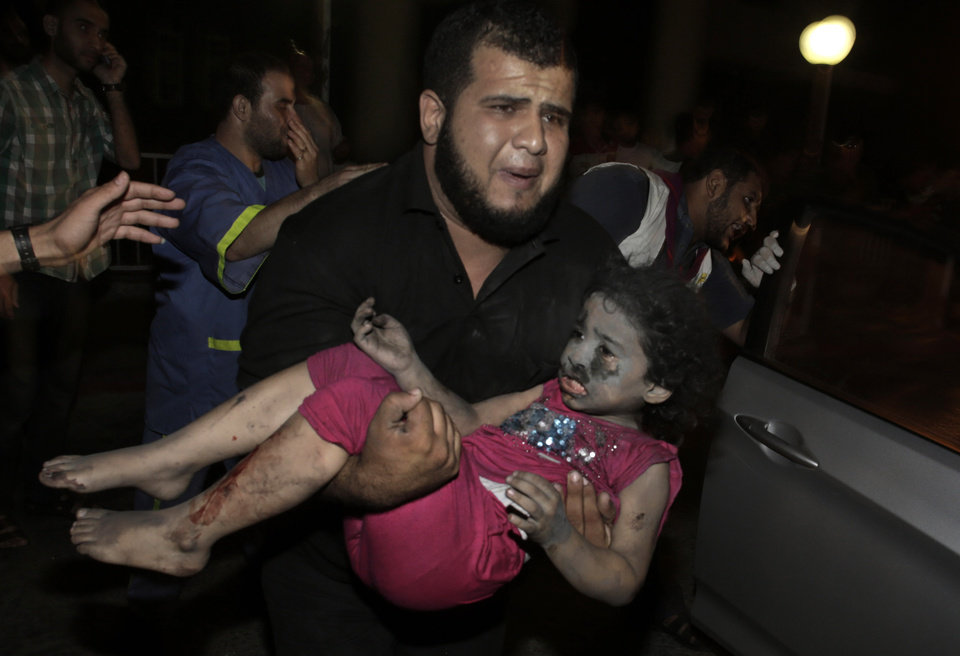 Photo - A Palestinian man carries an injured girl into the Shifa hospital following Israeli strikes which hit Gaza City, Tuesday, Aug. 19, 2014. Israel resumed its campaign of airstrikes in Gaza on Tuesday in response to a barrage of Palestinian rocket fire that shattered a truce. The sudden burst of fighting has threatened to derail an Egyptian effort to end a monthlong war between Israel and Hamas militants in Gaza. (AP Photo/Khalil Hamra)