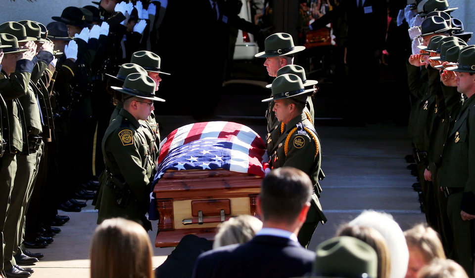 Photo -   U.S. Border Patrol agents lift the casket holding slain agent Nicholas Ivie during the funeral at The Church of Jesus Christ of Latter Day Saints in Sierra Vista, Ariz., on Monday, Oct. 8, 2012. (AP Photo/Arizona Daily Star,Mike Christy ) ALL LOCAL TV OUT; PAC-12 OUT; MANDATORY CREDIT