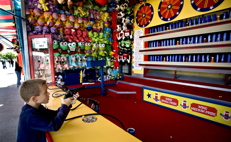 Photo - Zach Lathim, 6, of Boise, Idaho, plays a game in the midway at the 2009 Oklahoma State Fair at State Fair Park on Wednesday, Sept. 23, 2009, in Oklahoma City, Okla.  Photo by Chris Landsberger, The Oklahoman.