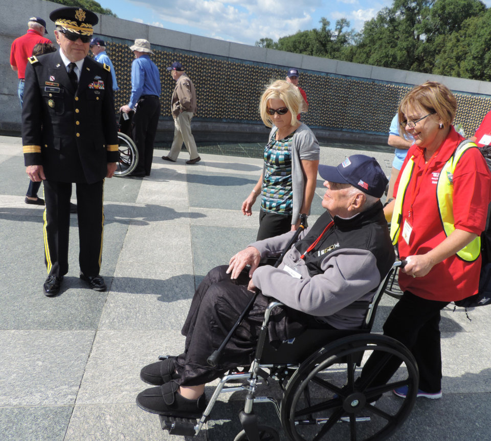 Photo - U.S. Army Ret. Brig. Gen David L. Cole, left, greets U.S. Army Ret. Col. John R. Burks of Pauls Valley accompanied by Lynn Sisney of Windsor, Colo. Wednesday, Oct. 8, 2014.  Photo by Bryan Painter, The Oklahoman