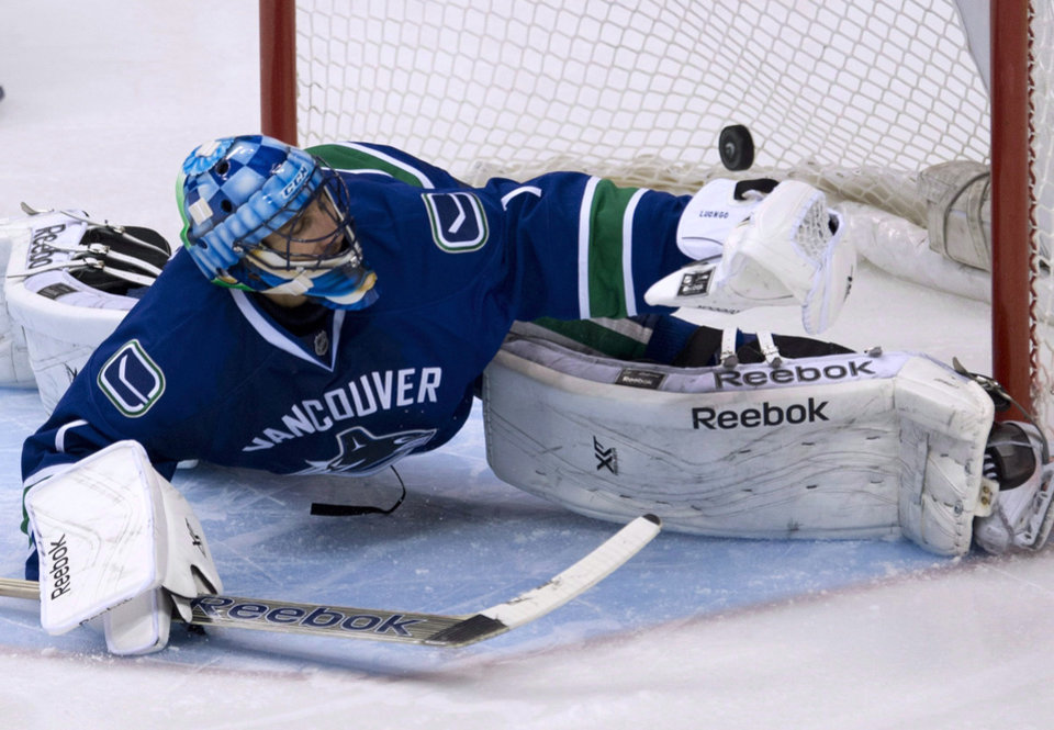 Photo - FILE - In this Nov. 17, 2013, file photo, a shot by Dallas Stars Erik Cole sails past Vancouver Canucks goalie Roberto Luongo during an NHL hockey game in Vancouver, British Columbia, Sunday, Nov. 17, 2013. The Canucks have traded Luongo to the Florida Panthers. (AP Photo/The Canadian Press, Jonathan Hayward)
