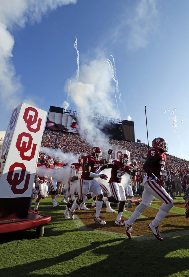 Photo - Sooners take the field amid fire and smoke for a college football game between the University of Oklahoma Sooners (OU) and the Louisiana Tech Bulldogs at Gaylord Family-Oklahoma Memorial Stadium in Norman, Okla., on Saturday, Aug. 30, 2014. Photo by Steve Sisney, The Oklahoman