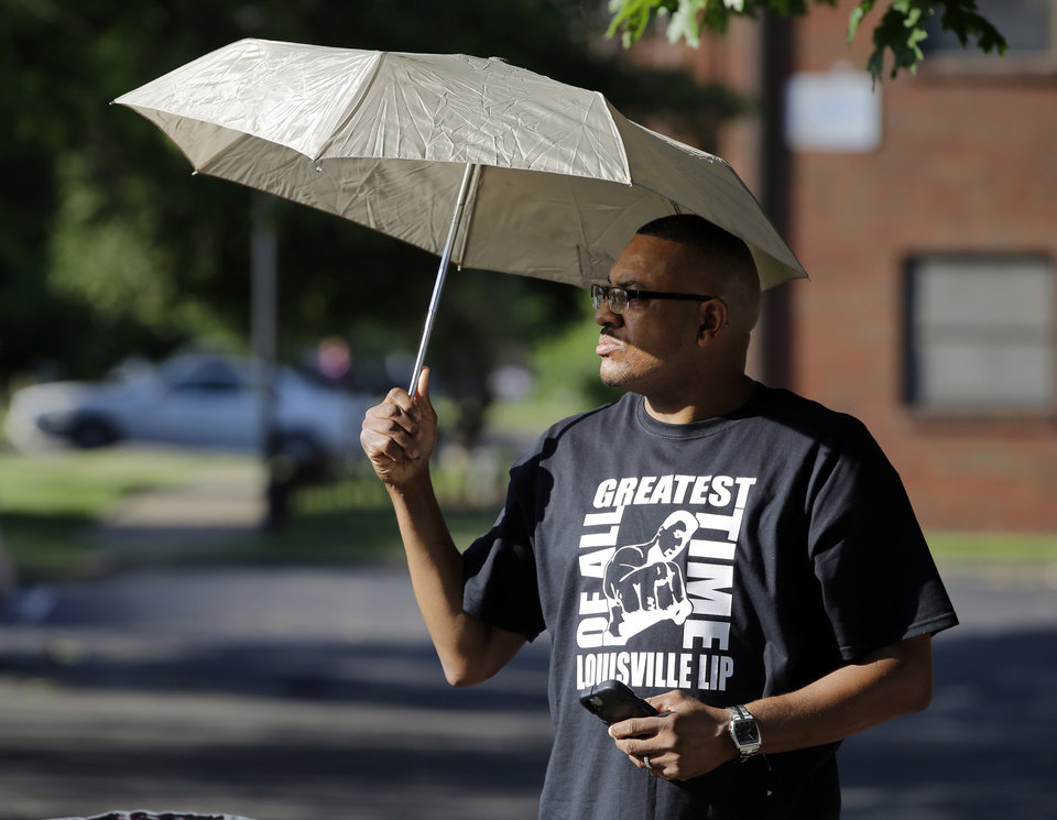 Photo - Dale James waits for the procession to pass with the hearse carrying the body of Muhammad Ali, Friday, June 10, 2016, in Louisville, Ky. (AP Photo/Darron Cummings)
