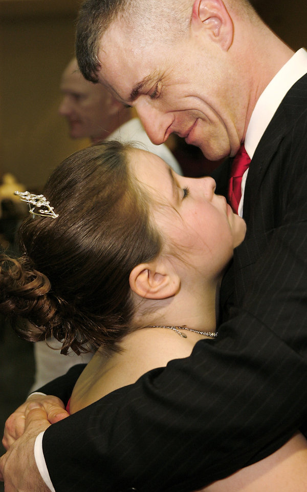 Photo - Brianna Zenzen, 9, closes her eyes as she is held close by her dad, Todd Zenzen during a slow dance at the Daddy-Daughter Dance at the Reed Center in Midwest City Saturday night, Feb. 7, 2009. Brianna lives in Moore, but attends Mid-Del Schools. The annual event is hosted by the Midwest City Parks and Recreation Department.   BY JIM BECKEL, THE OKLAHOMAN