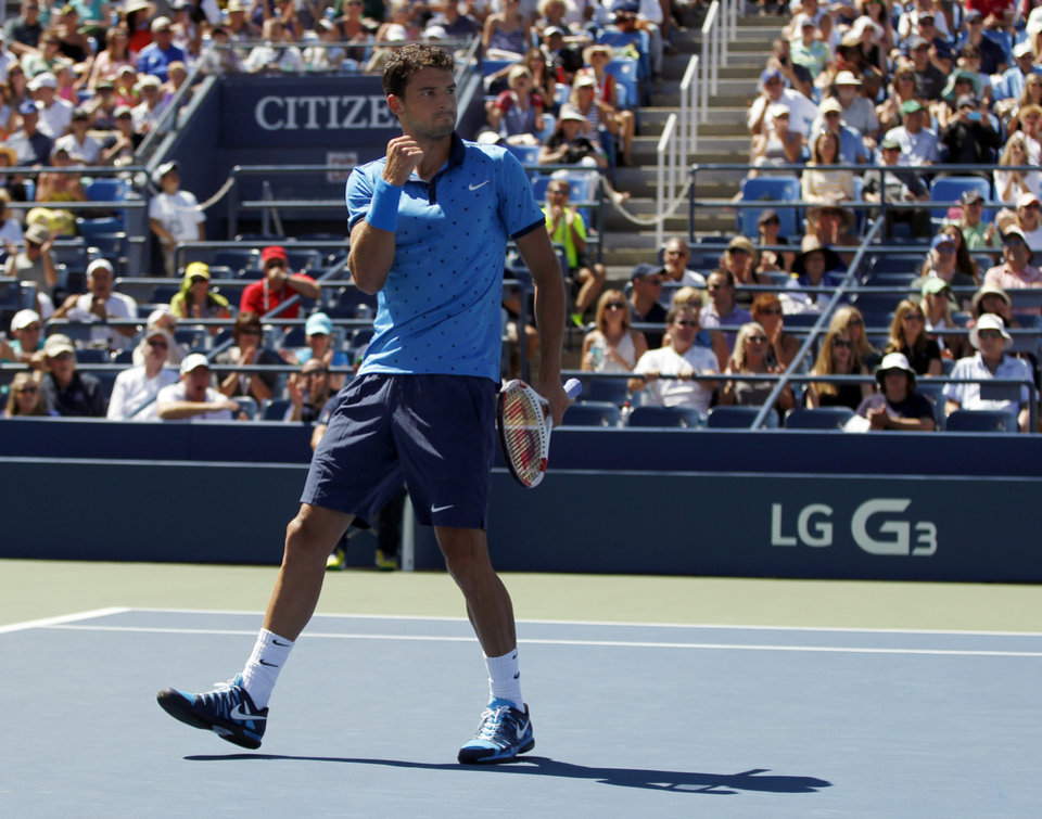 Photo - Grigor Dimitrov, of Bulgaria, reacts after a shot against Dudi Sela, of Israel, during the second round during the second round of the 2014 U.S. Open tennis tournament, Friday, Aug. 29, 2014, in New York. (AP Photo/Frank Franklin)