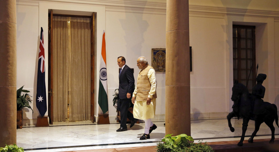 Photo - Indian Prime Minister Narendra Modi and his Australian counterpart Tony Abbott walk before a meeting in New Delhi, India, Friday, Sept. 5, 2014. Abbott met with Modi during a two-day state visit during which they are expected to sign a deal to allow the export of uranium to New Delhi for use in power generation. (AP Photo/Manish Swarup)