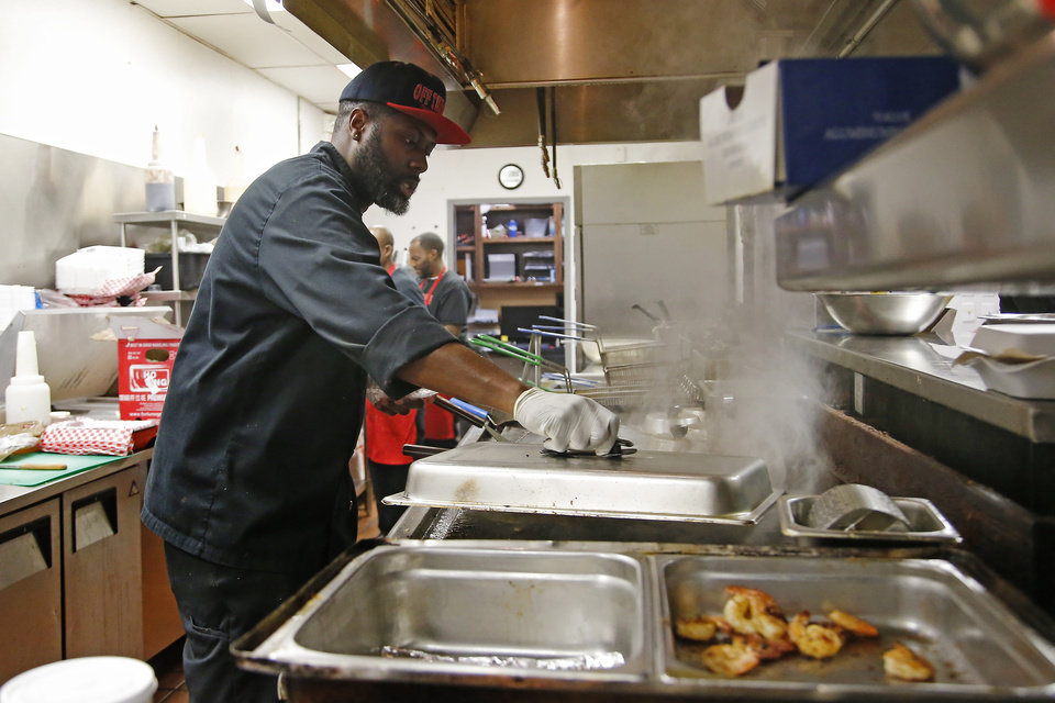Photo -  Chef Corey Harris prepares food at Off the Hook's south Oklahoma City location. [Photo by Bryan Terry, The Oklahoman]