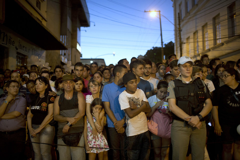 People gather outside the Kiss nightclub honoring the victims of early Sunday's fatal fire inside the club in Santa Maria, Brazil, Monday, Jan. 28, 2013. All the elements were in place for the tragedy at the Kiss nightclub early Sunday. The result was the world's worst fire of its kind in more than a decade, with 231 people dead and this southern Brazilian college town in shock and mourning.(AP Photo/Felipe Dana) ORG XMIT: XFD120