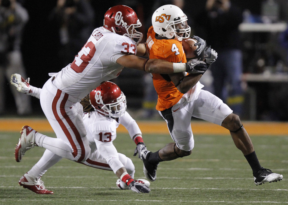 Photo - Oklahoma State's Justin Gilbert (4) runs a kick return past Oklahoma's Trey Millard (33) and Marcus Trice (13) during the Bedlam college football game between the University of Oklahoma Sooners (OU) and the Oklahoma State University Cowboys (OSU) at Boone Pickens Stadium in Stillwater, Okla., Saturday, Nov. 27, 2010. Photo by Chris Landsberger, The Oklahoman