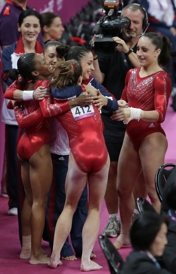 U.S. gymnasts celebrate after their routine on the vault during the Artistic Gymnastic women's team final at the 2012 Summer Olympics, Tuesday, July 31, 2012, in London. (AP Photo/Gregory Bull)