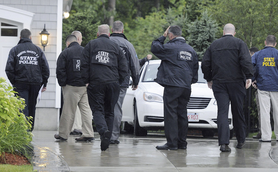 Photo - In this Tuesday, June 18, 2013 photo, state and local police gather outside the home of New England Patriot's NFL football player Aaron Hernandez in North Attleborough, Mass.  Police spent hours at the home Tuesday as another group of officers searched an industrial park about a mile away where a body was discovered the day before.  (AP Photo/The Sun Chronicle, Martin Gavin)