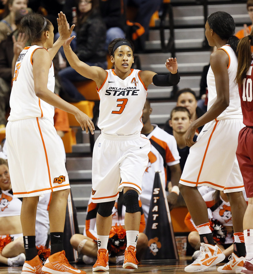 Photo - Oklahoma State's Tiffany Bias (3) celebrates with Kendra Suttles (31), left, and Toni Young (15) after a play during the Bedlam women's college basketball game between Oklahoma State University and the University of Oklahoma at Gallagher-Iba Arena in Stillwater, Okla., Saturday, Feb. 23, 2013. OSU beat OU, 83-62. Photo by Nate Billings, The Oklahoman