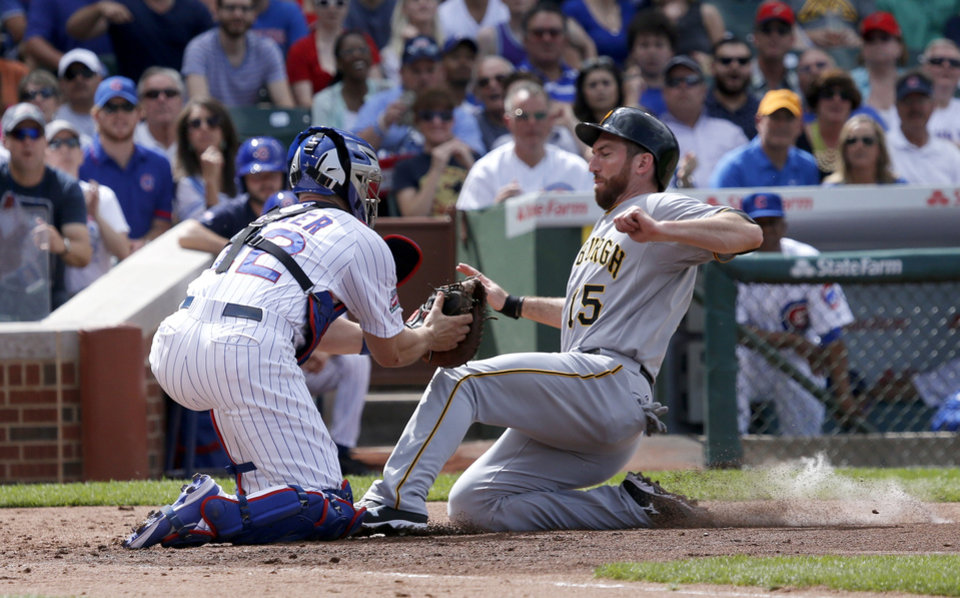 Photo - Chicago Cubs catcher John Baker, left, tags out Pittsburgh Pirates' Ike Davis at home plate during the second inning of a baseball game Friday, June 20, 2014, in Chicago. The play was upheld on video review. (AP Photo/Charles Rex Arbogast)