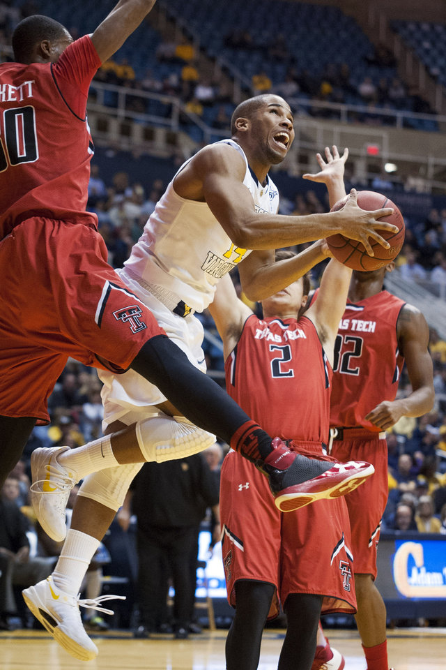 Photo - West Virginia's Gary Browne, right, looks to shoot during the second half of an NCAA college basketball game against Texas Tech, Wednesday, Jan. 22, 2014, in Morgantown, W.Va. West Virginia won 87-81. (AP Photo/Andrew Ferguson)