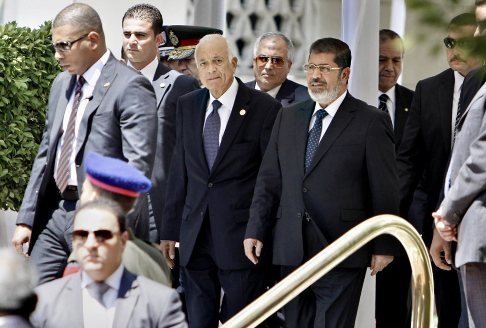 Photo -   Egyptian bodyguards surround President Mohammed Morsi, right, and Arab League Secretary-General Nabil Elaraby, second right, as they leave the Arab League headquarters in Cairo, Egypt, Wednesday, Sept. 5, 2012. Morsi says Syrian leader Bashar Assad must learn from