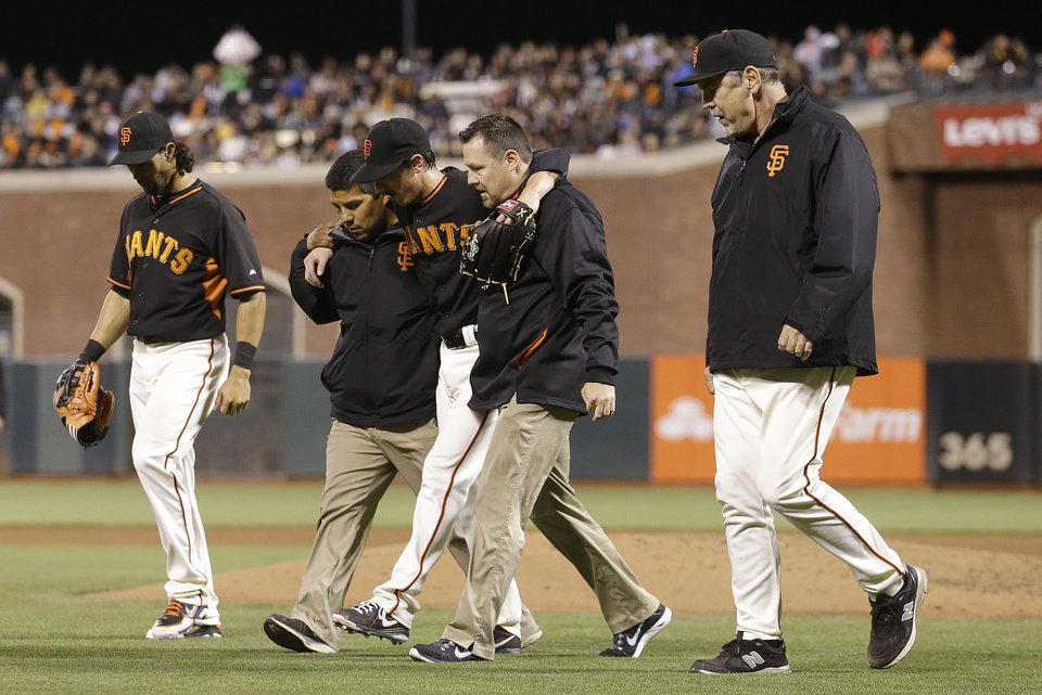 Photo - San Francisco Giants pitcher Tim Lincecum, center, walks off the field with trainers, center fielder Angel Pagan, left, and manager Bruce Bochy, right, after being struck by a ball hit by Oakland Athletics' Daric Barton during the fourth inning of a spring exhibition baseball game in San Francisco, Friday, March 28, 2014. (AP Photo/Jeff Chiu)